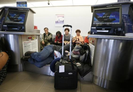 Hành khách trể chuyến bay nằm chờ sau khi một vụ xả súng xảy ra tại sân bay quốc tế Los Angeles, Mỹ.