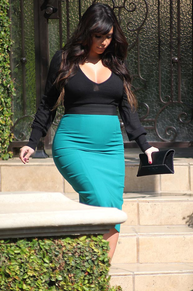 Kim Kardashian in a tight black top and turquoise skirt