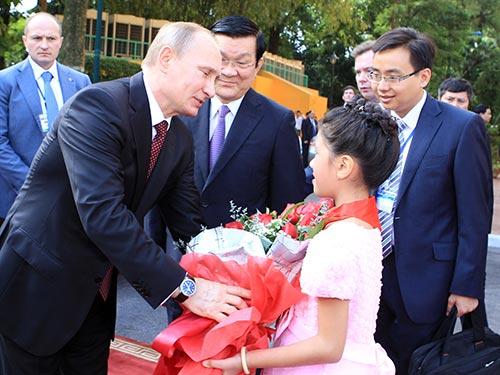 Một em nhỏ tặng hoa chào mừng Tổng thống Putin.