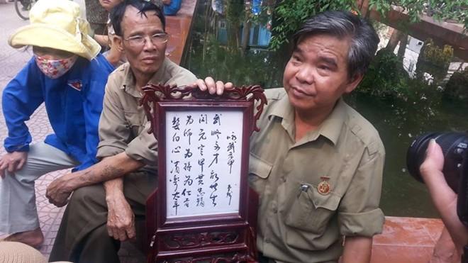 Ông Đinh Hữu Phương, sinh năm 1946, mang theo bức thư họa tri ân Đại tướng, vào vườn hoa để theo dõi Lễ viếng. Ảnh: Trí Thức