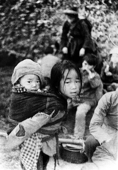 Hai chị em cháu bé cùng bà con sơ tán khỏi thị xã Cao Bằng sáng 17/7 (Ảnh: Mạnh Thường)