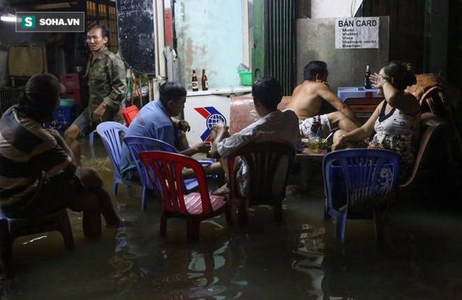 Người Sài Gòn đeo ủng ngồi giữa nhà ngập nước đọc báo, xem tivi - Ảnh 1.
