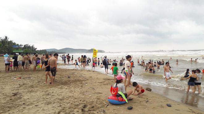 [Ảnh] Mặc bão vào, hàng trăm du khách liều mình tắm biển rồi bỏ chạy khi có sóng lớn - Ảnh 1.