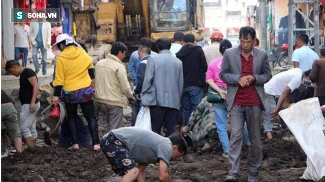 Bất chấp đoạn đường đang được tu sửa, người dân vẫn đổ xô ra đào cuốc vì lý do bất ngờ - Ảnh 1.