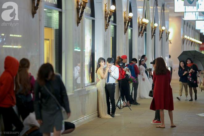 Hà Nội vào mùa cưới, một mét vuông mấy chục cô dâu chen nhau tạo dáng, bất chấp gió mưa - Ảnh 2.