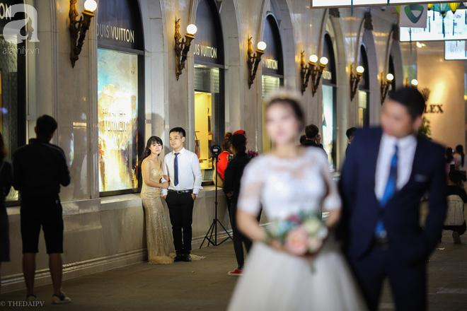 Hà Nội vào mùa cưới, một mét vuông mấy chục cô dâu chen nhau tạo dáng, bất chấp gió mưa - Ảnh 3.