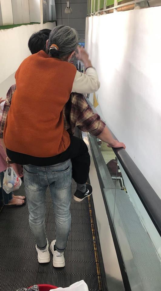 Bà sợ thang cuốn, cháu trai dịu dàng đưa lên lưng cõng - hình ảnh gây xúc động sáng nay - Ảnh 1.