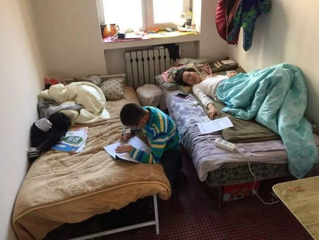 Cậu bé vừa học bài, vừa chăm sóc mẹ.
