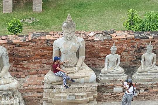 """Nữ du khách bị """"ném đá"""" vì ngồi vào lòng tượng Phật - Ảnh 1."""