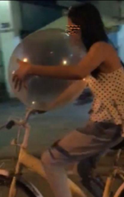 Xôn xao clip cô gái vừa đi xe đạp vừa thản nhiên hít bóng cười trên đường phố - Ảnh 1.