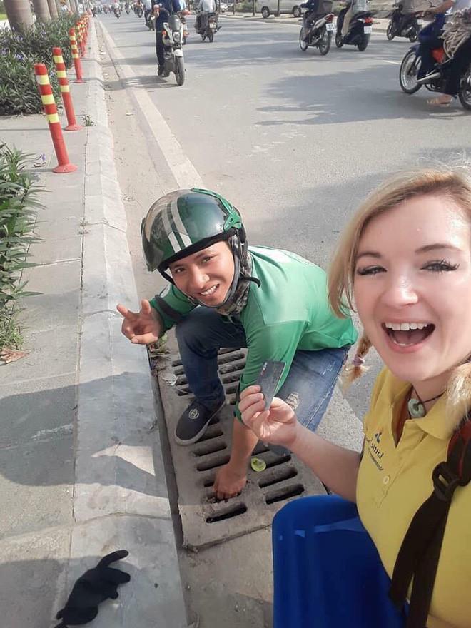 Hình ảnh đẹp: Hai tài xế GrabBike chui xuống cống để nhặt đồ hộ nữ du khách nước ngoài - Ảnh 2.