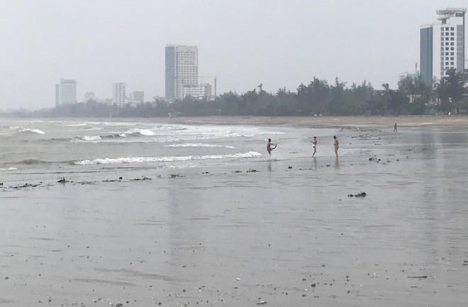 Do ảnh hưởng của bão số 3: Trời đang mưa dày hạt nhưng nhiều du khách vẫn bất chấp để xuống biển tắm.