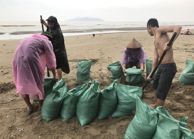 Tin bão số 3 sắp đổ bộ: Nhiều thanh niên ra bờ biển xúc cát để chuẩn bị chằng chống nhà cửa.