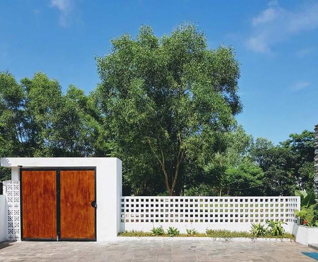 Cổng rào bằng gỗ mang vẻ đẹp gần gũi, giản dị kết hợp cùng gạch thông gió cho cảm nhận tươi mát khi cộng hưởng cùng mảng xanh của cây cối trong khuôn viên ngôi nhà.