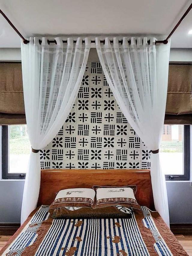 Phòng ngủ cũng được trang trí với gạch bông thông gió. Giường ngủ gỗ đơn giản về kiểu dáng nhưng vẫn nổi bật nhờ họa tiết trên chăn, gối, rèm ngủ trắng cho cảm nhận dễ chịu.