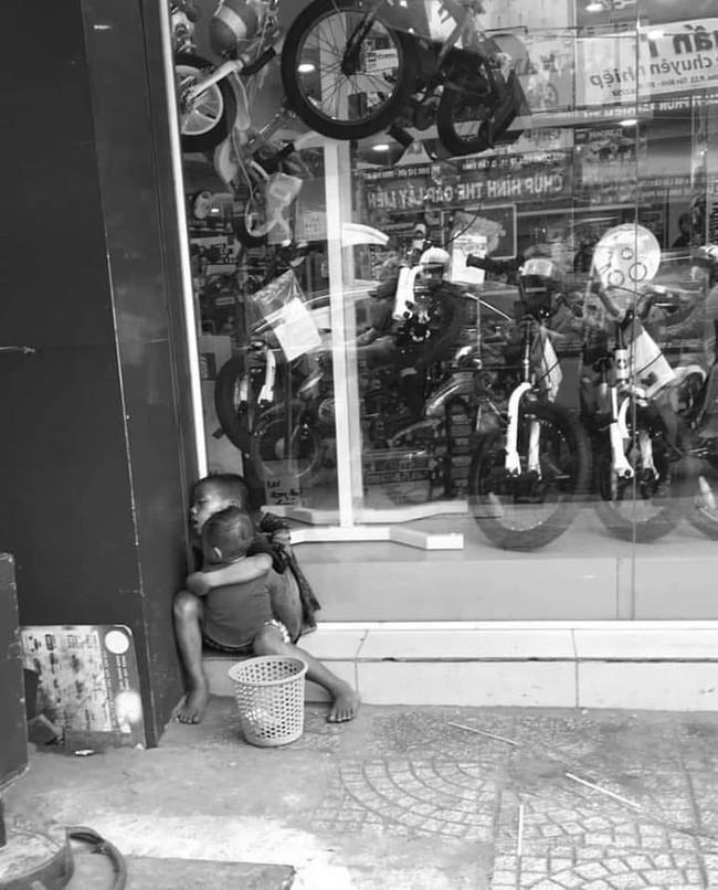 Câu chuyện sau bức ảnh hai đứa trẻ lem luốc, ôm nhau ngủ trên vỉa hè giáp Tết làm trái tim người mẹ nhói đau - Ảnh 1.