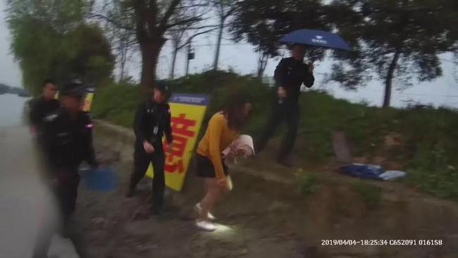 Cô Liu (áo vàng) được cảnh sát đưa lên bờ sau khi lao xuống sông cùng chồng.