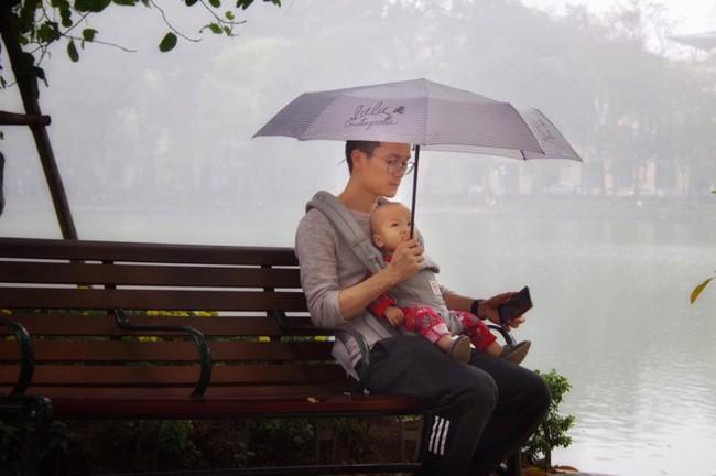 Địu con trước ngực dạo bờ hồ ngày mưa bụi, sắc mặt của bố bỉm sữa mới là thứ gây chú ý - ảnh 1