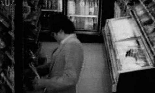 Một người đàn ông lạ đặt sản phẩm lên kệ cửa hàng tạp hóa.