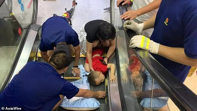 Bé trai bị kẹt tay vào thang cuốn.