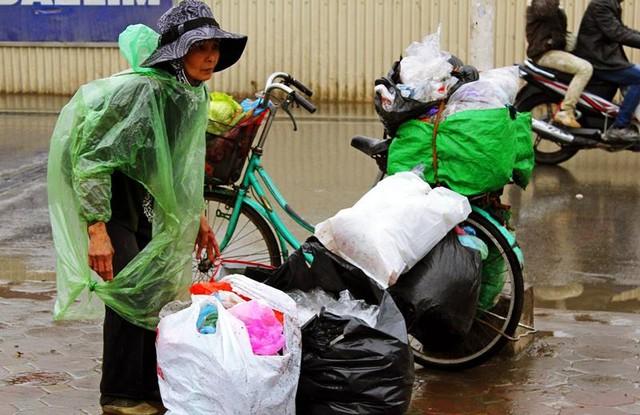 Một người nhặt các túi nilon, thùng giấy mà người dân đi thả cá vứt lại về bán phế liệu.