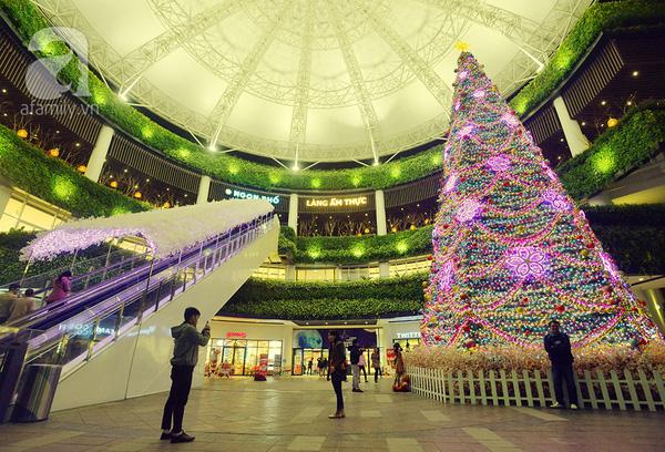 Nằm cạnh lối vào trung tâm thương mại Aeonmall Long Biên, cây thông Noel cao 15m được trang trí bằng dây thông, đèn led, hoa sakura, những quả bóng nhựa nhiều màu, với tông màu chủ đạo là tím hồng huyền ảo.
