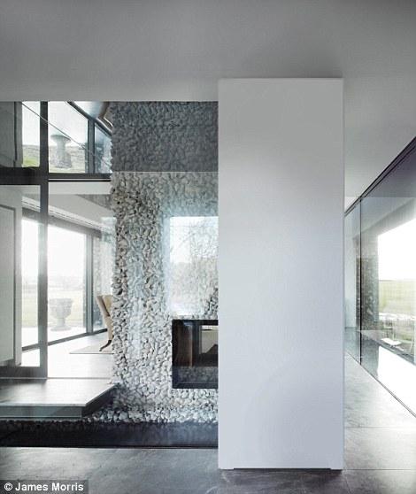 Xung quanh nhà được trang trí bằng những bức tường đá xám, xen kẽ là những bức tường trắng, làm nổi bật sàn gỗ màu tối.