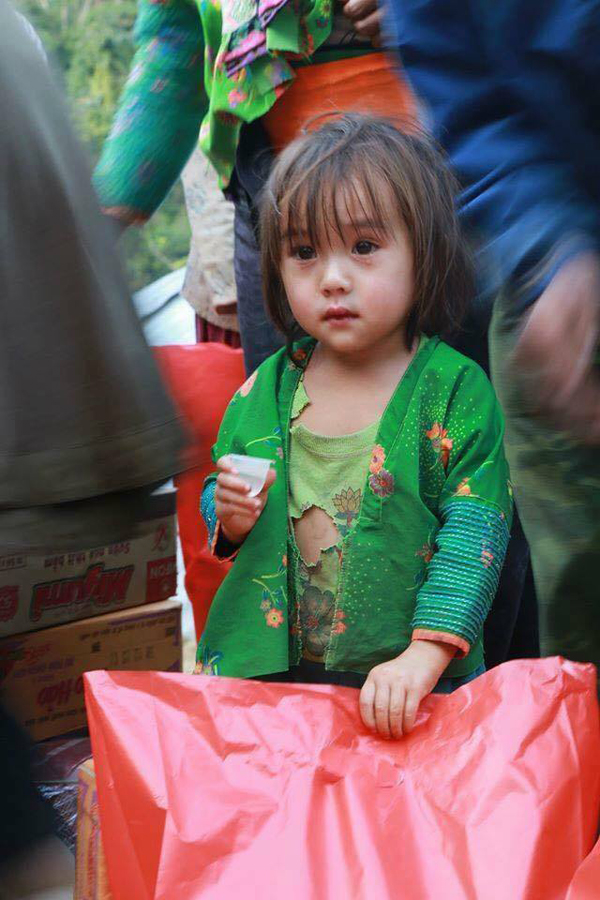 Hình ảnh bé gái mặc áo rách đứng nhận quà từ thiện. Ảnh: Facebook.