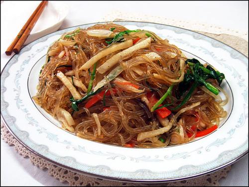 Japchae làm từ mì, xào với rau, thịt bò, nước tương, đường và dầu vừng. Tùy  vào sở thích bạn có thể thưởng thức nóng hoặc lạnh.