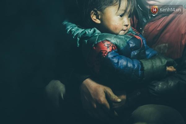 Ánh mắt rụt rè của bé gái đang được nép vào vòng tay mẹ.