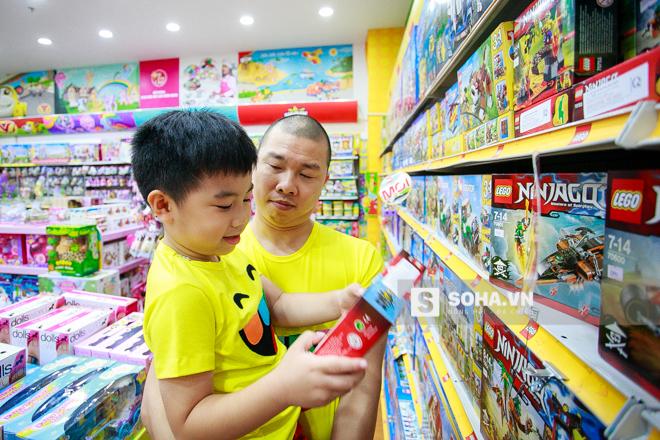 2 bố con tranh thủ rẽ vào một cửa hàng đồ chơi và mua một bộ lego.
