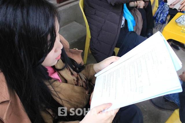 Nữ diễn viên tranh thủ học thoại, tập thoại trong lúc chờ các thành viên khác trong đoàn hóa trang và chuẩn bị bối cảnh.