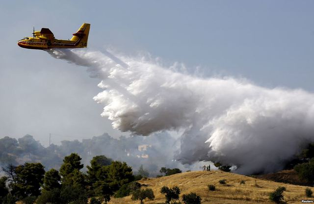 Người dân địa phương nhìn máy bay thả nước chữa cháy rừng tại vùng Argolida, Hi Lạp.