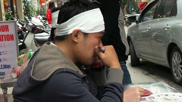 Một người cháu của cụ Cúc ngồi bên đường và buồn bã trước đám tang