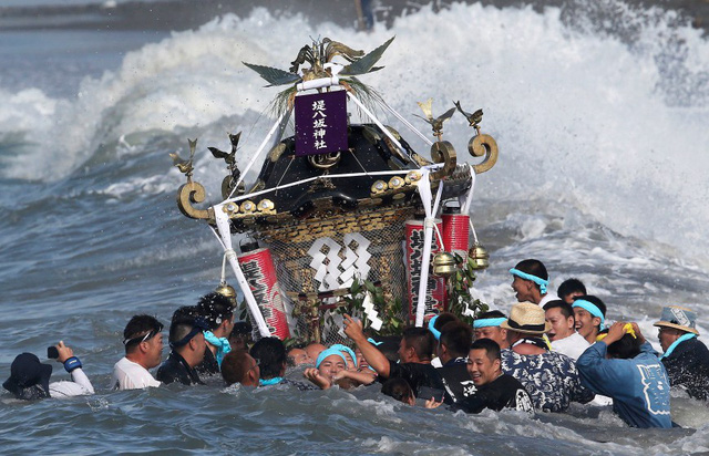 Mọi người khiên đền thờ di động xuống biển trong một nghi lễ truyền thống tại lễ hội Hamaori, Tokyo, Nhật Bản.