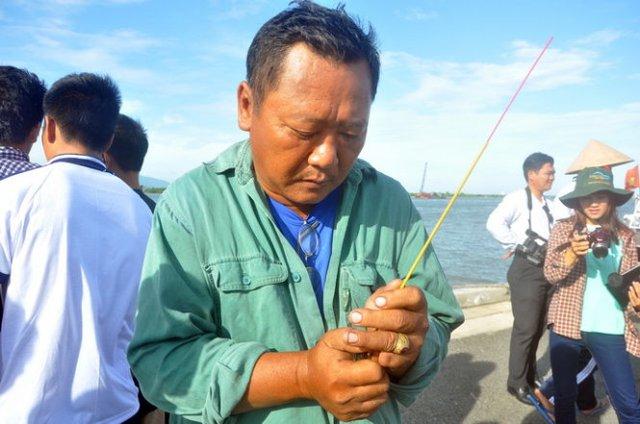 Thuyền viên Nguyễn Đức Kỳ (51 tuổi, quê Đồng Tháp) thắp nén hương viếng những đồng nghiệp xấu số - Ảnh: Đ.Thanh
