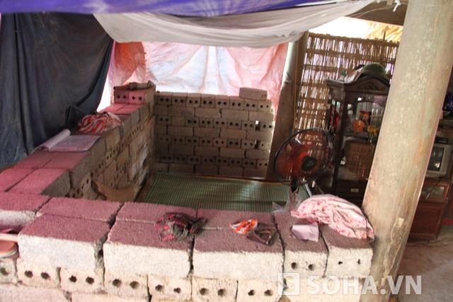 Nhà bà Minh nghèo đến nỗi sung quanh nhà, giường ngủ không có tường hay cửa mà phải xếp gạch để che chắn.