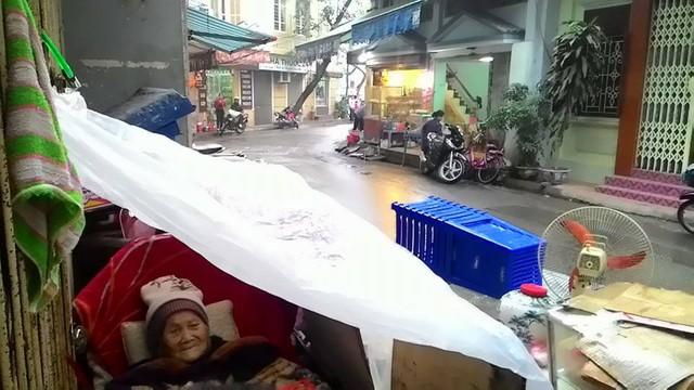 Cụ Cúc đang ngồi bên trong chiếc áo mưa che trên đầu, đã hơn 1 ngày