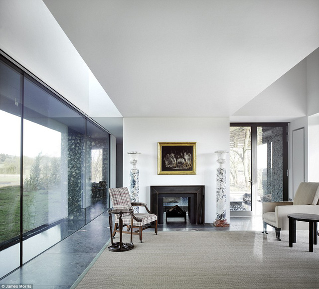 Phòng khách của căn nhà được trang trí bằng màu trắng và những tấm kính trong suốt.