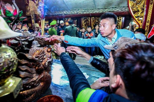 Thanh gậy gỗ linh thiêng được đặt trên bàn thờ trong đền Thiên Trường được nhiều người ra sức dùng tiền lẻ để quét vào cầu may - Ảnh: Nguyễn Khánh