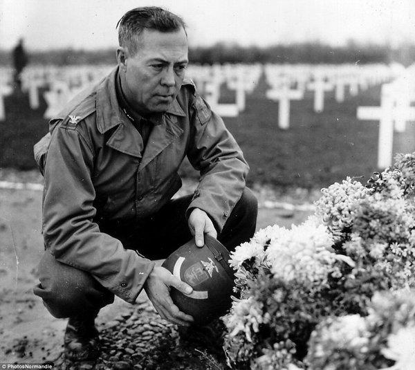 Một sĩ quan quân đội Mỹ dừng trước một ngôi mộ tạm.