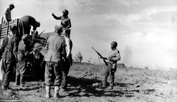 Lính Mỹ gốc Phi đưa tù binh Phát xít Đức lên xe tải ở Colleville-sur-Mer, Pháp.