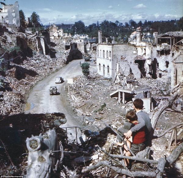 Hai cậu bé nhìn xe quân đội Mỹ đi qua thị trấn Agneaux bị phá hủy nặng nề sau cuộc giao tranh ác liệt giữa quân Đồng minh và Phát xít.