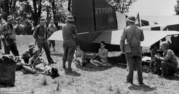 Hai phụ nữ đeo kính ngồi cạnh chiến đấu cơ Waco được vây quanh bởi các binh sĩ Mỹ.