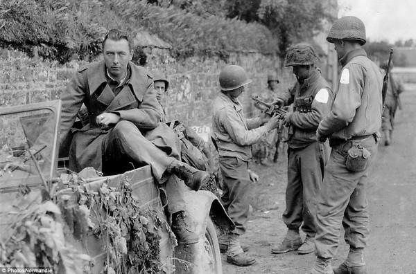 Lính thủy đánh bộ Mỹ kiểm tra một khẩu súng tịch thu được của lính Đức tại Notre-Dame de Cenilly.