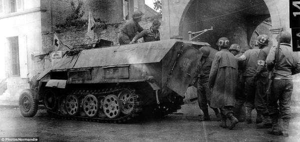 Binh sĩ Canada giúp một sĩ quan Đức xuống xe sau khi bị bắt tại Chambois.