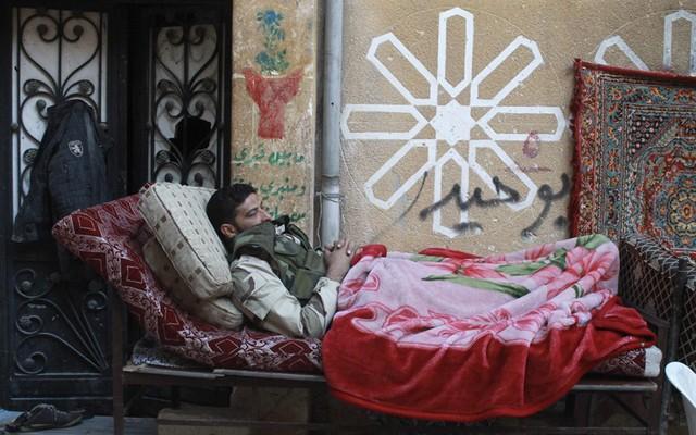 Một chiến binh phiến quân nằm nghỉ trên đường phố ở Aleppo, Syria.