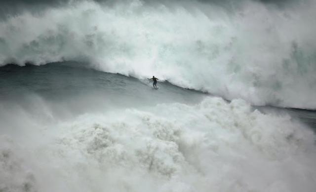 Một người đàn ông lướt ván trên con sóng lớn ở Praia do Norte, in Nazare, Bồ Đào Nha.