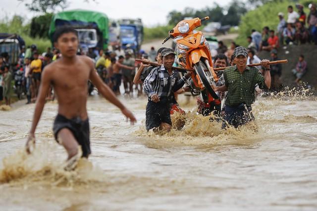 Mọi người khiêng một chiếc xe máy qua đường phố ngập lụt sau mưa lớn ở thị trấn Minhla, Myanmar.