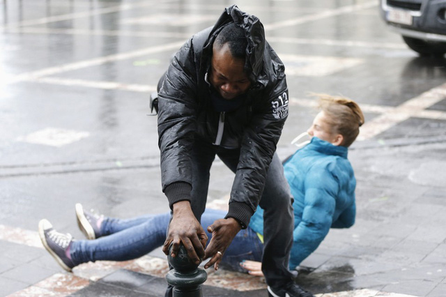 Một người bấu vào trụ trước một phụ nữ bị ngã do gió bão mạnh ở Brussels, Bỉ.